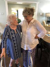 Lisa Hawkins and her mother, Dorothy Thompson, hug and smile lovingly at each other in a blue living room. Mrs. Thompson is gently holding on to a walker.