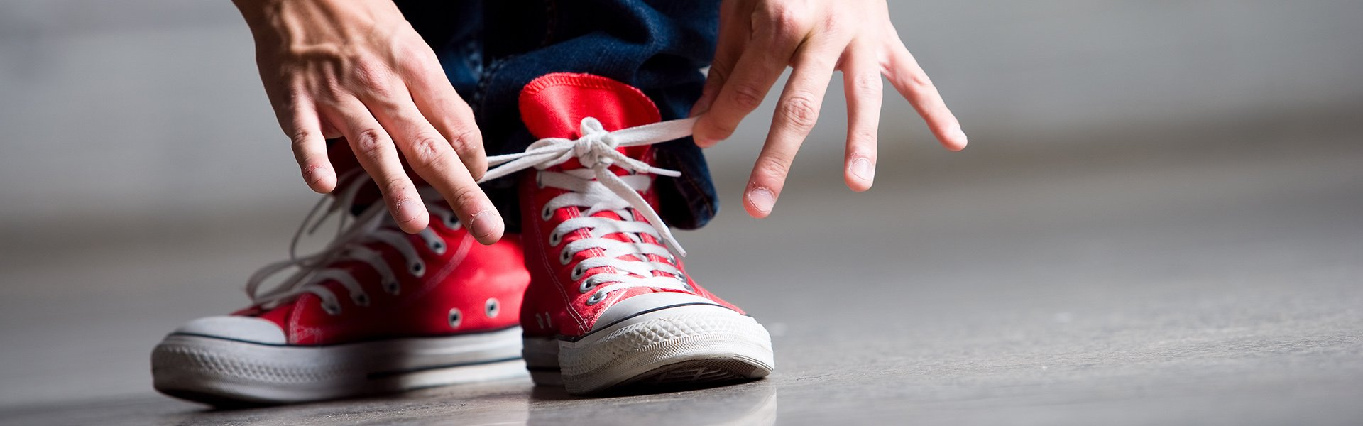 Hands tying white shoestrings on red sneakers with white soles