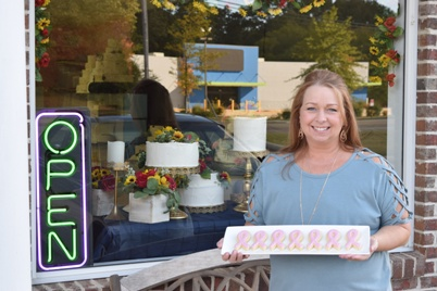 Holly Whitworth in front of her bakery window, holding a plate of pink breast cancer awareness cookies she plans to donate.