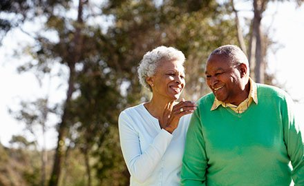 Black, older couple walking together and smiling. The woman has short white hair and a blue top and the man is wearing a green sweater.