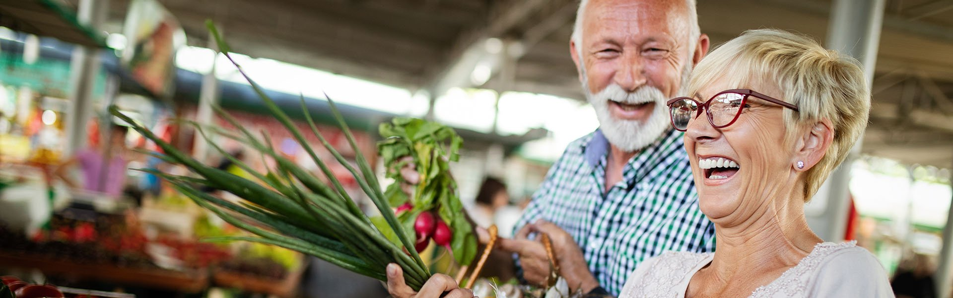 An older couple laughing while shopping at a farmer's market.