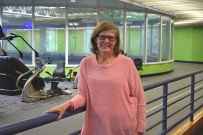 Eileen Bailey in a pink sweater smiling after a walk on the NMMC Wellness Center track.