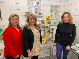 group photo of Patti Hawkins, Ashley Frazier and Jennifer Groover with the pottery butterflies designed by Jennifer.